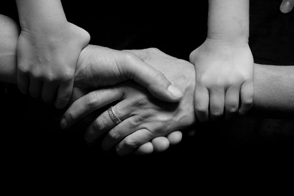 Image of hands, adults shaking hands with a child holding each adult's wrist, used to depict a parenting plan